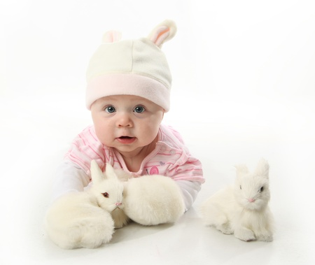 Portrait of an adorable baby girl wearing a bunny rabbit costume and petting two white bunnies photo