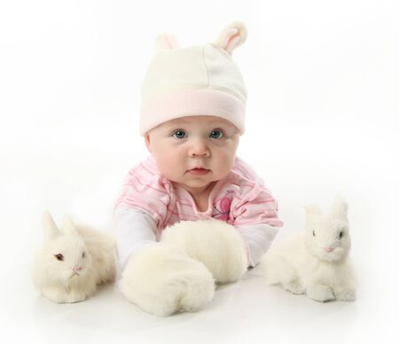 xmas baby: Portrait of an adorable baby girl wearing a bunny rabbit costume and petting two white bunnies  Stock Photo