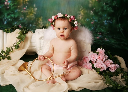 baby girls smiley face: Beautiful young girl wearing angel wings and flower halo with somber expression