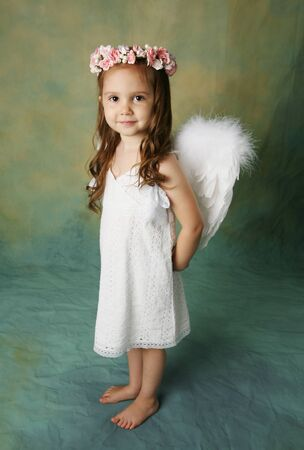 angel girl: Beautiful young girl wearing angel wings and flower halo with smile happy expression