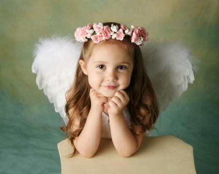 Mooi meisje dragen engel vleugels en bloem halo met glimlach gelukkig expressie Stockfoto