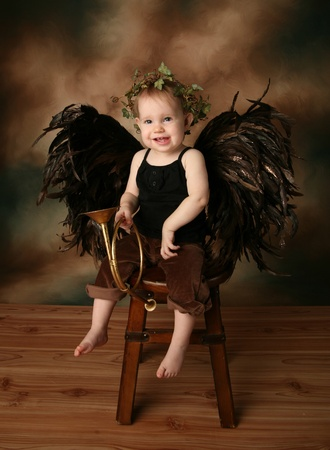 Beautiful young girl wearing angel wings and ivy halo with smile happy expression