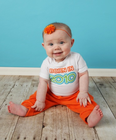 Portrait of an adorable baby girl sitting in front of a turquoise blue wall wearing a shirt that says Born in 2010 photo