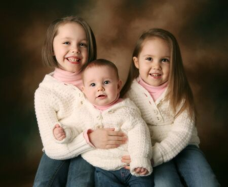 Studio portrait of three cute young sisters hugging each other wearing white cream sweaters on a brown background, baby, toddler, and preschool aged 版權商用圖片