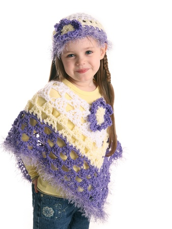 Portrait of an adorable toddler girl wearing handmade crochet clothes, a shawl and hat in purple and yellow Standard-Bild