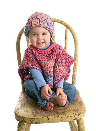 baby on chair: Adorable baby girl wearing handmade crochet clothes, a shawl and hat Stock Photo
