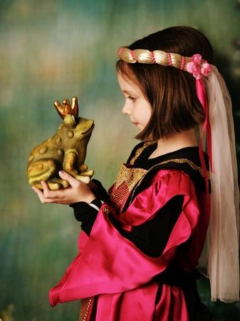 Ritratto di una giovane ragazza di prescolare carino vestita come una principessa in un abito rosa e oro, posa e baciare un principe rana indossando una corona