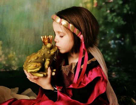 Portrait of a cute young preschool girl dressed as a princess in a pink and gold gown, posing and kissing a frog prince wearing a crown