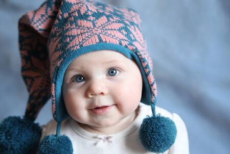 Portrait of an adorable baby girl with big blue eyes wearing a knit pink and blue winter hat