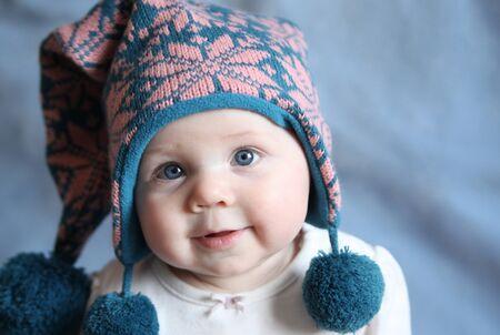 ropa invierno: Retrato de una ni�a adorable con grandes ojos azules, llevaba un sombrero de invierno malla de Rosa y azul