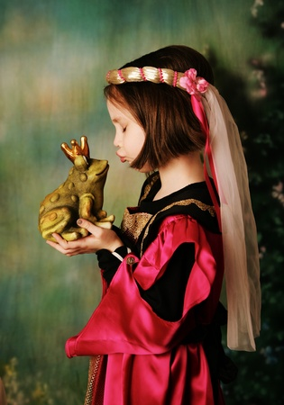 frog prince: Portrait of a cute young preschool girl dressed as a princess in a pink and gold gown, posing and kissing a frog prince wearing a crown