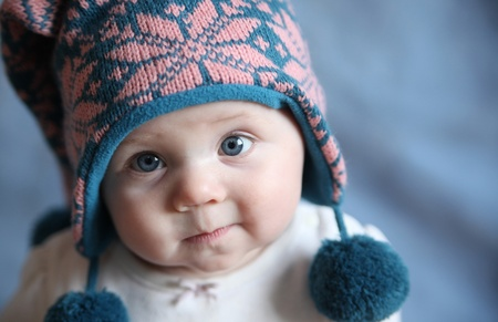 Portrait of an adorable baby girl with big blue eyes wearing a knit pink and blue winter hat photo