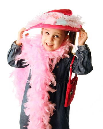 Portrait of an adorable preschool girl playing dress up with a fancy hat, purse, and pearl necklace isolated on white