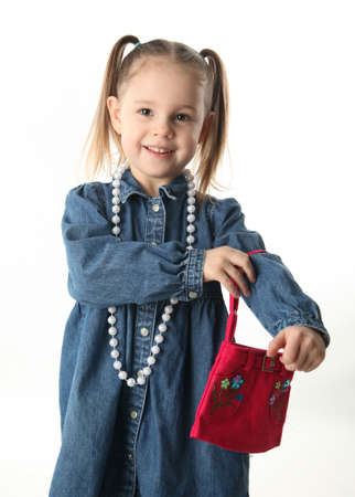 Portrait of an adorable preschool girl playing dress up with a purse and pearl necklace isolated on white