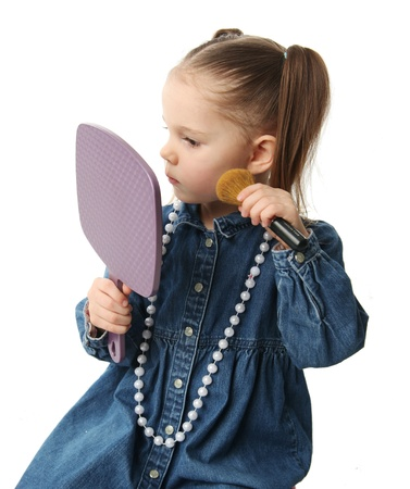 Portrait of a cute little preschool girl applying makeup and looking in a mirror Stock Photo - 8809286