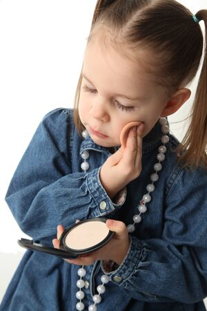 Portrait of a cute little preschool girl applying makeup and looking in a mirror photo