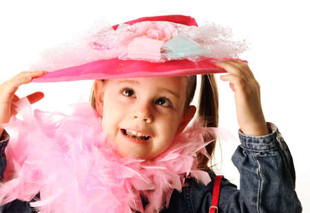 Portrait of an adorable preschool girl playing dress up with a fancy hat, purse, and pearl necklace isolated on white Stock Photo - 8809312