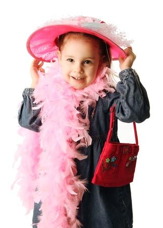 Porträt eines adorable Vorschule Mädchen spielen Dress up mit einer Phantasie Hat, Geldbeutel und Perlenkette, isoliert auf weiss Standard-Bild