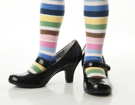Toddler girl wearing bright colored striped tights trying on mother's high heel shoes Standard-Bild