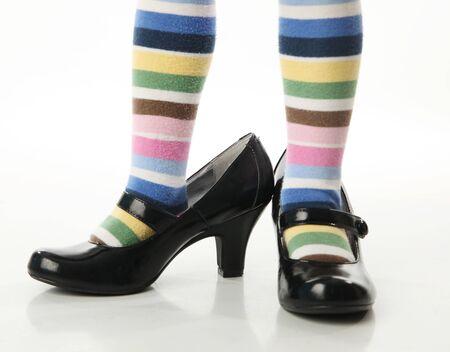 big game: Ragazza bambino indossa brillante collant a righe colorate cercando su scarpe tacco alto della madre