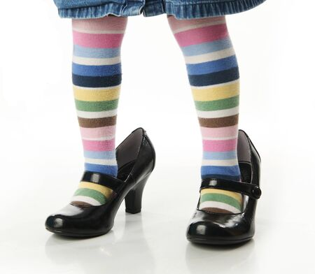big game: Toddler girl wearing bright colored striped tights trying on mothers high heel shoes