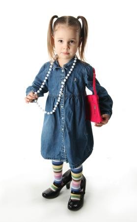 ni�as jugando: Retrato de una chica de preescolar adorable jugando vestido con una madre zapatos, bolso y collar de perlas aislados en blanco
