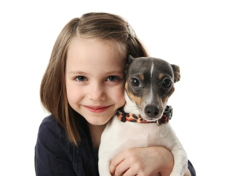 Portrait of a beautiful young girl snuggling with a cute terrier puppy dog, isolated on white in studio photo