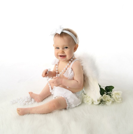 Soft portrait of a baby girl wearing white angel wings and white pearl necklace photo