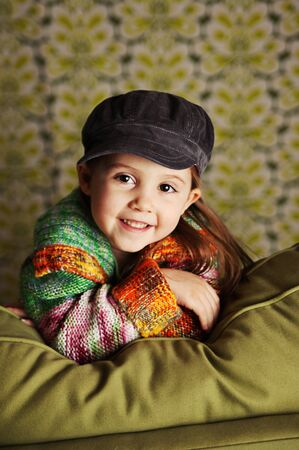 Portrait of a pretty preschool girl wearing a bright sweater and hat sitting on a green couch photo