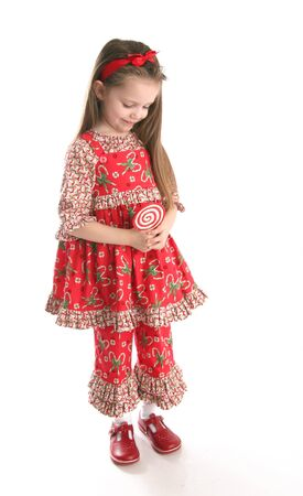 Adorable preschool girl wearing a Christmas holiday outfit posing holding a lollipop, isolated on white Stock Photo - 8809330