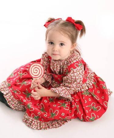 Adorable toddler girl wearing a Christmas holiday outfit posing, isolated on white Standard-Bild
