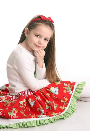 Adorable preschool girl wearing a Christmas holiday outfit posing, isolated on white photo