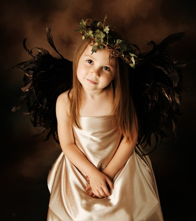 Portrait of a beautiful young girl dressed up as an angel with brown wings and a gold dress, wearing an ivy crown