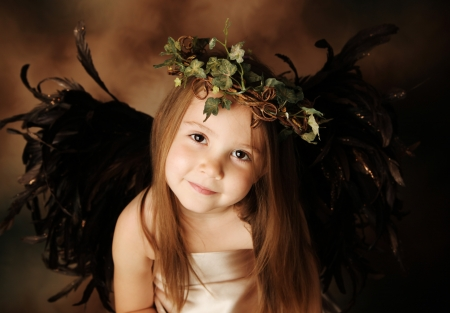 little girl smiling: Portrait of a beautiful young girl dressed up as an angel with brown wings and a gold dress, wearing an ivy crown