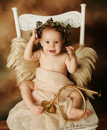 Portrait of a beautiful young girl dressed up as an angel with brown wings and a gold dress, wearing an ivy crown photo
