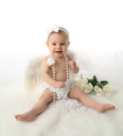 Soft portrait of a baby girl wearing white angel wings and white pearl necklace