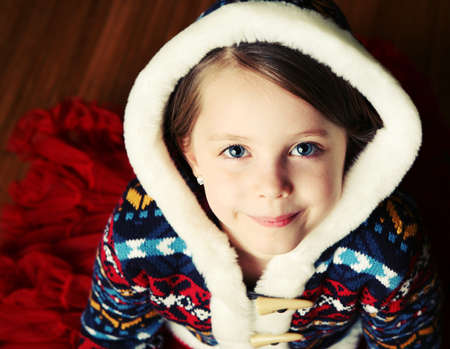 Portrait of a pretty young girl wearing a sweater with fur hood