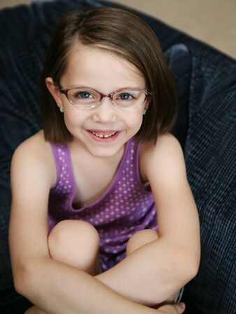 Little girl sitting on a sofa wearing purple eyeglasses Standard-Bild