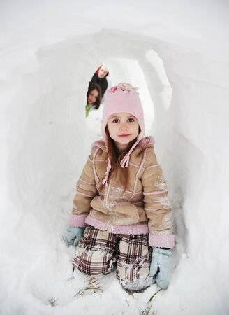 Father and two daughters playing in a snow fort tunnel