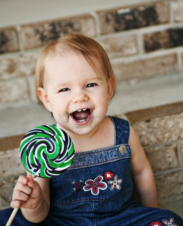 Toddler girl eating a messy lollipop sucker