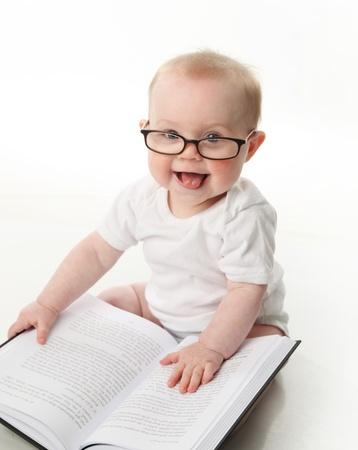 Retrato de un adorable bebé sentado uso de anteojos y mirando a un libro, aislado en blanco