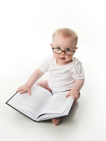 kids reading book: Portrait of an adorable baby sitting up wearing eyeglasses and looking at a book, isolated on white