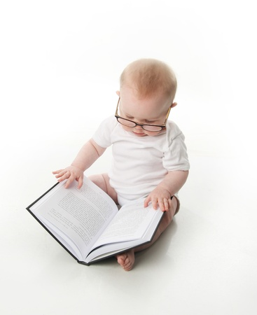 smart girl: Portrait of an adorable baby sitting up wearing eyeglasses and looking at a book, isolated on white