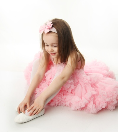 Portrait of an adorable preschool age girl playing dress up wearing a ballet tutu, isolated on white Stock Photo - 9939726