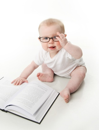 Portrait of an adorable baby sitting up wearing eyeglasses and looking at a book, isolated on white Editorial