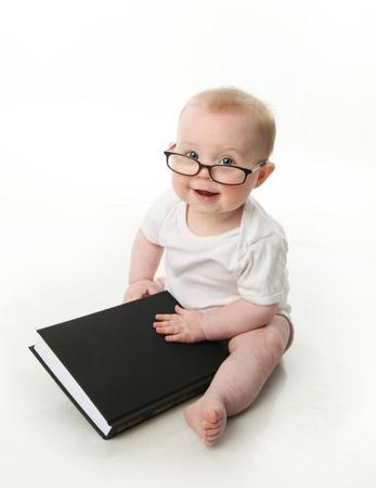 bebe sentado: Retrato de un adorable beb� sentado llevaba anteojos y mirando un libro, aislado en blanco
