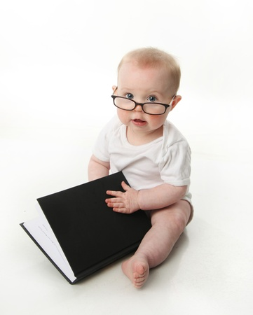 Portrait of an adorable baby sitting up wearing eyeglasses and looking at a book, isolated on white photo