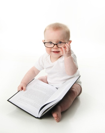 Portrait of an adorable baby sitting up wearing eyeglasses and looking at a book, isolated on white