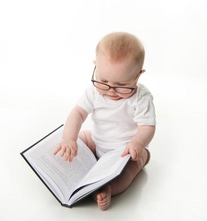 glass eye: Retrato de un adorable beb� sentado llevaba anteojos y mirando un libro, aislado en blanco