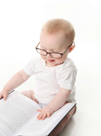 Portrait of an adorable baby sitting up wearing eyeglasses and looking at a book, isolated on white Stock Photo - 9939572